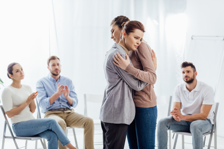 Photo pour women hugging while group of people sitting and applauding during therapy session - image libre de droit