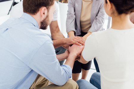 Photo pour partial view of people sitting and stacking hands during group therapy session - image libre de droit