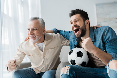 Photo pour happy retired man watching championship and cheering with handsome son holding football - image libre de droit