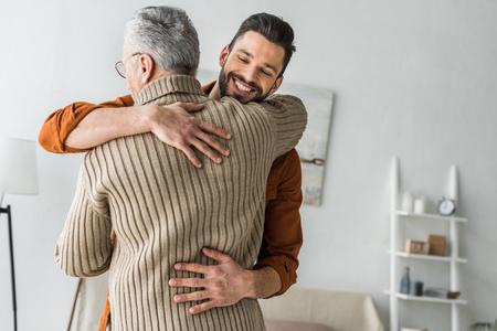 Photo pour happy bearded man smiling while hugging elder father at home - image libre de droit