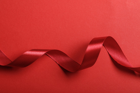 Photo for top view of wavy silk red ribbon on red background with copy space - Royalty Free Image