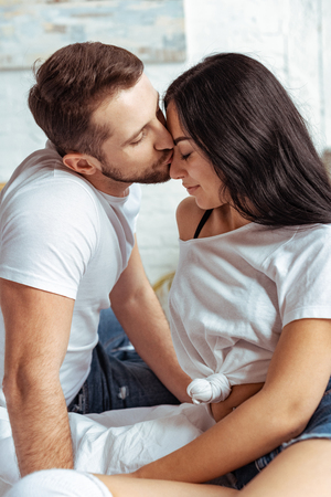 Photo for handsome man kissing beautiful and brunette woman in bedroom - Royalty Free Image