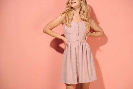 Photo pour cropped view of blonde woman with hands on hips in pink dress on pink background - image libre de droit