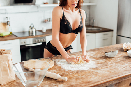 Partial view of sexy woman in black lingerie kneading dough in kitchen