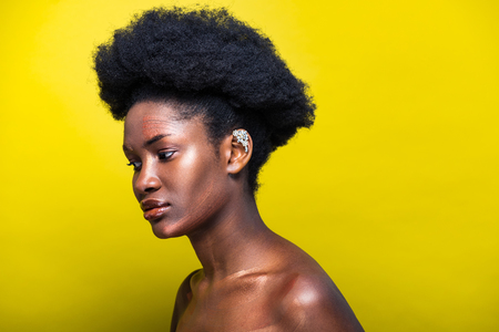 Photo for Pensive attractive african american woman with ear cuff on yellow - Royalty Free Image