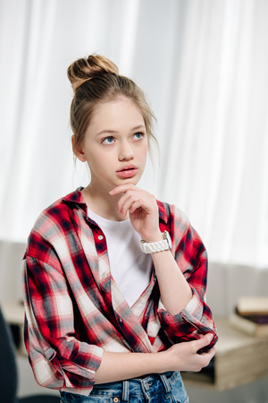 Photo pour Pensive teenage kid in red checkered shirt looking away - image libre de droit