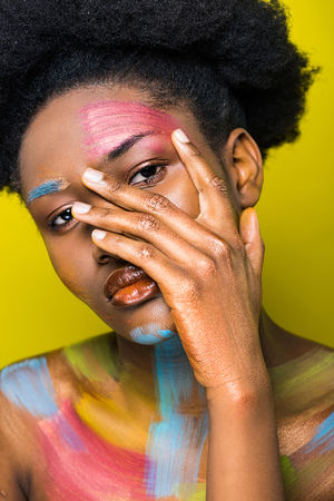 Foto de Pretty african american woman with body art touching face isolated on yellow - Imagen libre de derechos