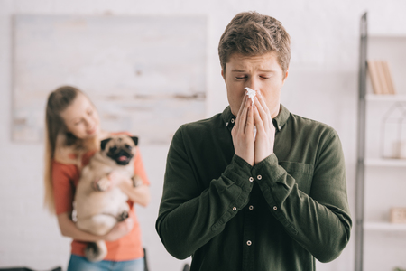 Photo pour selective focus of man sneezing in tissue with closed eyes while standing near woman with dog - image libre de droit