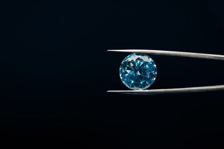 Photo for colorful blue sparkling diamond in tweezers isolated on black - Royalty Free Image