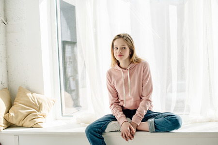 Foto per Pensive teenage kid in jeans sitting on window sill and looking away - Immagine Royalty Free
