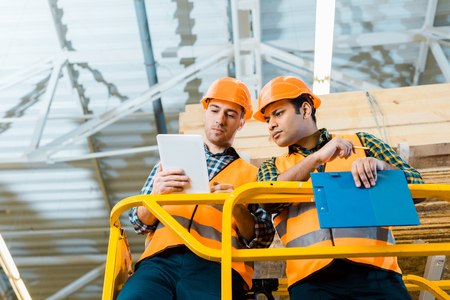 Photo pour thoughtful multicultural workers using digital tablet while standing on scissor lift in warehouse - image libre de droit