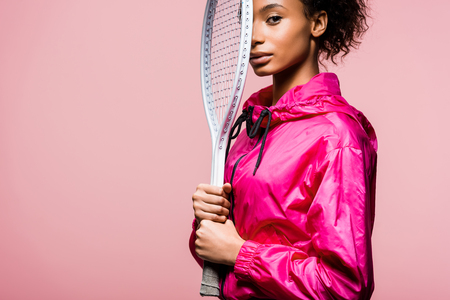 Foto de Beautiful African American sportswoman looking at camera and holding tennis racket isolated on pink with copy space - Imagen libre de derechos