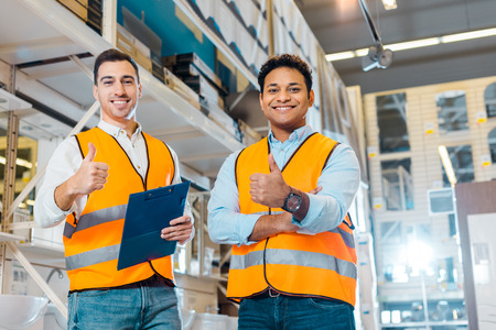 Photo pour Cheerful multicultural warehouse workers showing thumbs up and looking at camera - image libre de droit