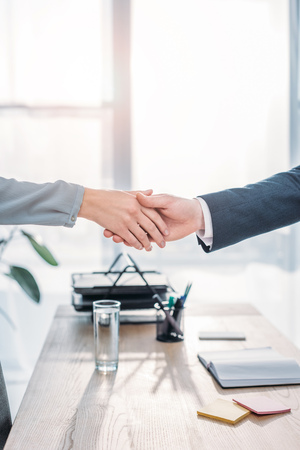 Photo pour cropped view of recruiter and employee shaking hands in modern office - image libre de droit