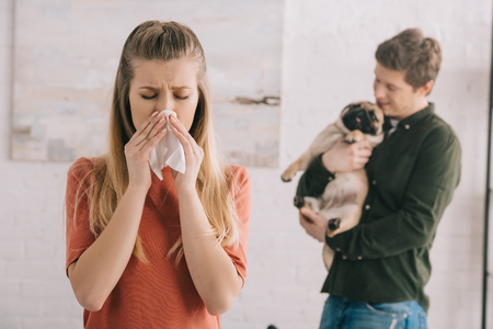 Photo pour selective focus of blonde girl allergic to dog sneezing in white tissue near man with cute pet - image libre de droit