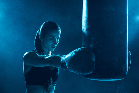Foto de Female boxer in boxing gloves training with punching bag - Imagen libre de derechos