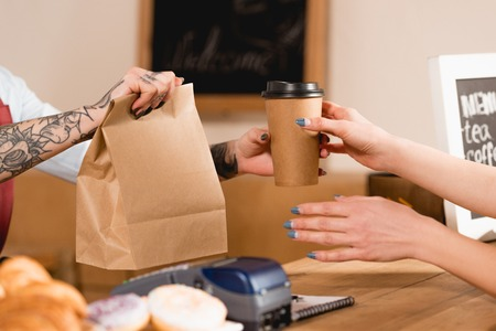 Photo pour Partial view of barista holding paper bag and disposable cup near customer - image libre de droit