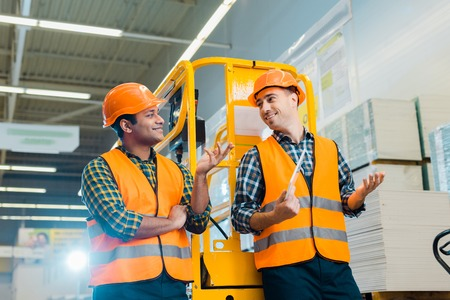 Photo pour Cheerful multicultural workers talking and gesturing while standing near scissor lift - image libre de droit