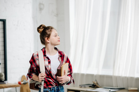 Photo pour Teenage schoolgirl in checkered shirt with backpack holding books - image libre de droit