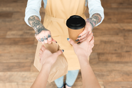 Photo pour Cropped view of tattooed waitress giving paper bag and disposable cup to customer - image libre de droit