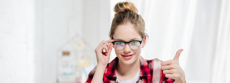 Foto de Panoramic shot of teenager in glasses showing thumb up and looking at camera - Imagen libre de derechos