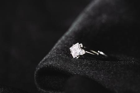 Foto de Engagement ring with pure shiny diamond on black cloth - Imagen libre de derechos