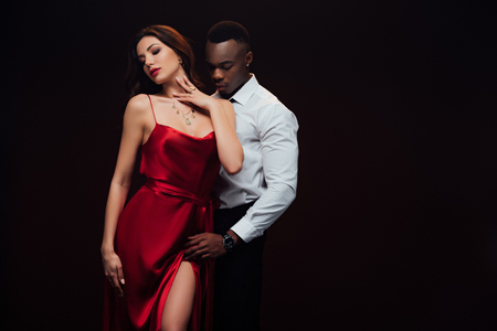 Photo pour Beautiful seductive interracial couple in formal wear posing isolated on black with copy space - image libre de droit