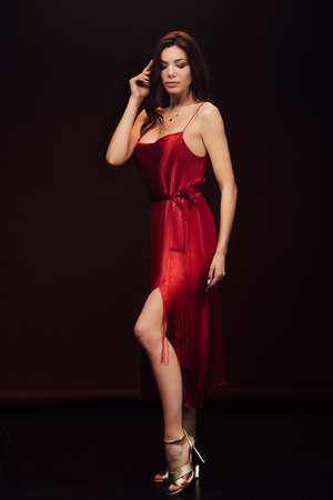 Foto de Beautiful sensual woman in red dress posing with eyes closed isolated on black background - Imagen libre de derechos