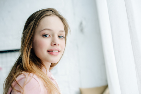 Photo pour Joyful teenage kid in pink hoodie looking at camera with smile - image libre de droit