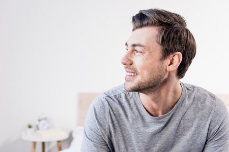 Photo for Handsome man in grey t-shirt smiling and looking away at home - Royalty Free Image