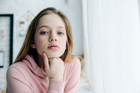 Photo pour Teenage child in casual pink hoodie looking at camera - image libre de droit