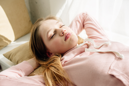 Photo pour Tired teenage kid lying on cushion with closed eyes - image libre de droit