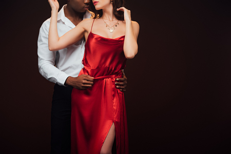 Foto de Partial view of African American man embracing woman in red dress isolated on black with copy space - Imagen libre de derechos