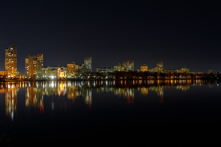 Photo for Picturesque dark cityscape with illuminated buildings, river and night sky - Royalty Free Image