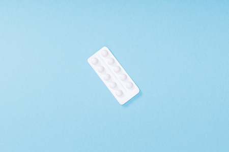 Top view of blister with pills on blue surface background