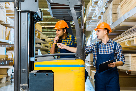 Photo pour Indian warehouse worker sitting in forklift machine near colleague pointing with pencil - image libre de droit