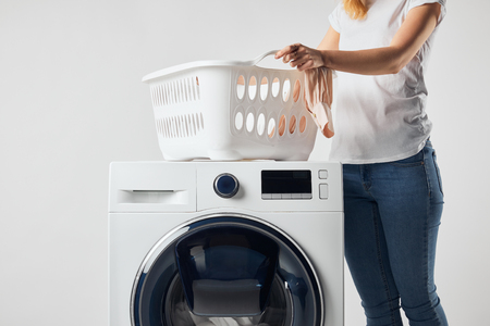 Photo pour Partial view of woman with landry basket and washing machine isolated on grey - image libre de droit