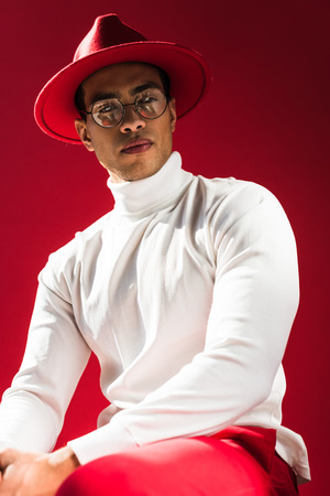 Photo pour fashionable mixed race man in hat and glasses sitting and posing isolated on red - image libre de droit