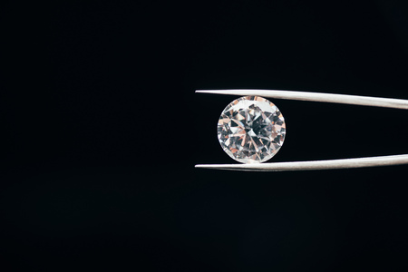 Foto de Transparent pure shiny diamond in tweezers isolated on black background - Imagen libre de derechos