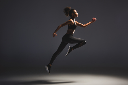 Photo for Side view of beautiful athletic African American sportswoman jumping on black background - Royalty Free Image