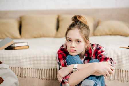 Foto de Bored teenager in checkered shirt sitting near bed and embracing knees - Imagen libre de derechos
