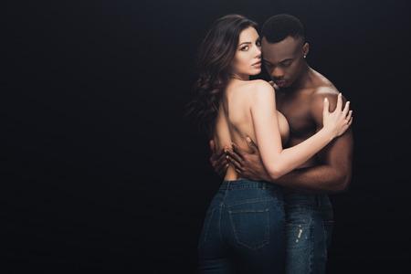 Foto de beautiful seductive half-naked interracial couple embracing isolated on black with copy space - Imagen libre de derechos