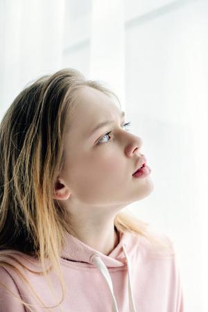 Photo pour Pensive teenage kid in pink hoodie looking away - image libre de droit