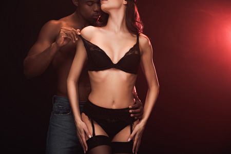 Cropped view of African American man undressing sexy woman in lingerie on dark with red light and copy space