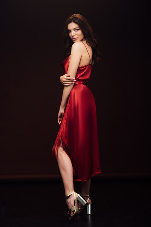 Photo pour Beautiful sensual woman in red dress posing and looking at camera isolated on black background - image libre de droit