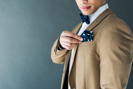 Foto de cropped view of stylish mixed race man in suit adjusting napkin isolated on grey with copy space - Imagen libre de derechos