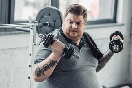 Foto de Obese tattooed man exercising with dumbbells at sports center - Imagen libre de derechos