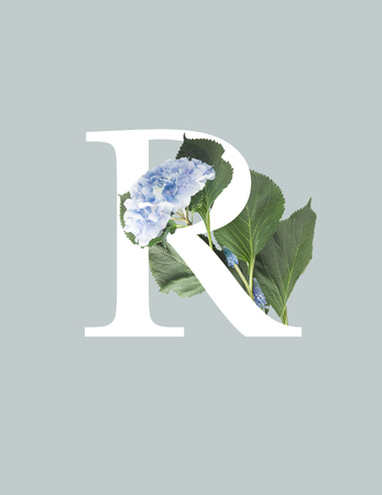 Foto de white letter R with blue hydrangea flowers and green leaves isolated on grey - Imagen libre de derechos