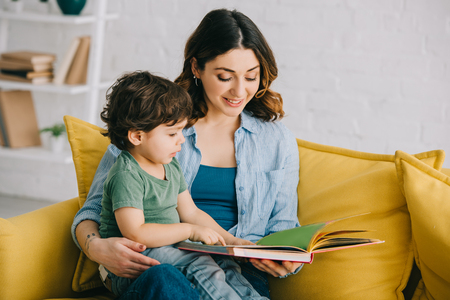 Photo pour Mom and son sitting on yellow sofa and reading book - image libre de droit