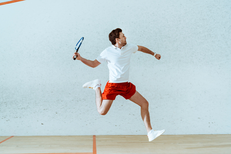 Photo pour Sportsman in polo shirt jumping while playing squash in four-walled court - image libre de droit